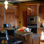 Kitchen remodeling in Naperville, IL. Rough beams, distressed cabinetry, custom corbels & wire drawer accents.